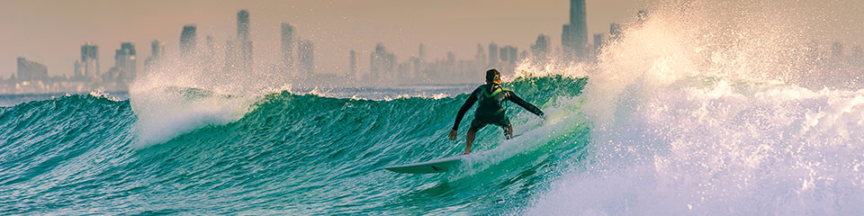 Surfer with Gold Coast City skyline in the background.