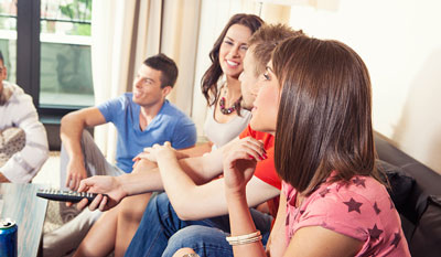 Students in an apartment watching TV.