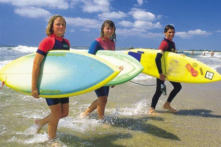 Beach living in Wollongong, with three students emerging from the surf with boards in hand.